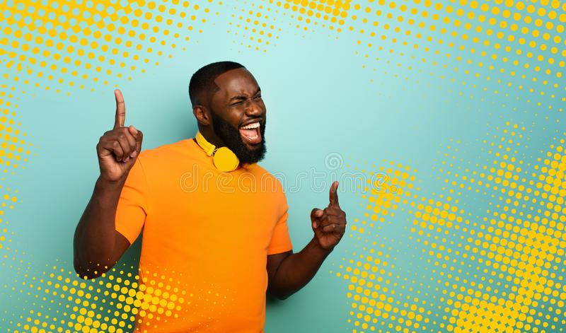 Boy with yellow headset listens to music and dances with energy on cyan background. Boy with yellow headset listens to music and dances with energy stock photos
