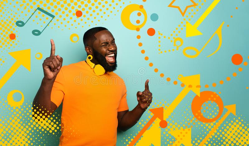 Boy with yellow headset listens to music and dances with energy on cyan background with pop shapes. Boy with yellow headset listens to music and dances with royalty free stock image