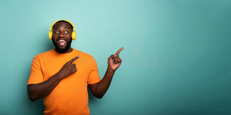 Boy with yellow headset listens to music and indicates something. With hands royalty free stock photography