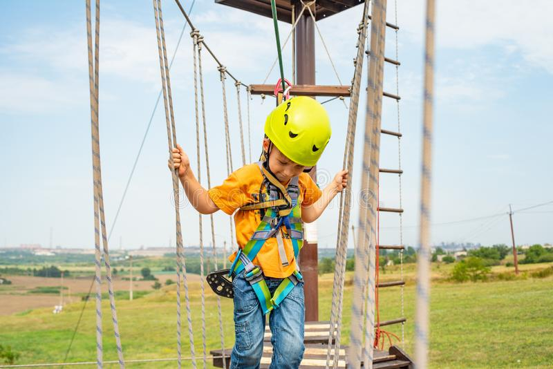 A boy in a yellow helmet overcomes an obstacle on the cable car in an extreme park. stock images