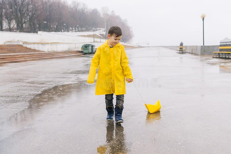 A boy in a yellow raincoat plays a large paper boat in a puddle. A toy. Yellow paper boat on a string. Embankment, street, outdoors, walk stock photos