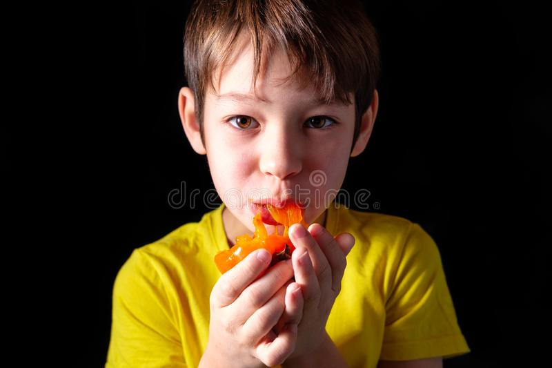 The boy in the yellow shirt is eating the orange fruit of the persimmon. On black background royalty free stock photo