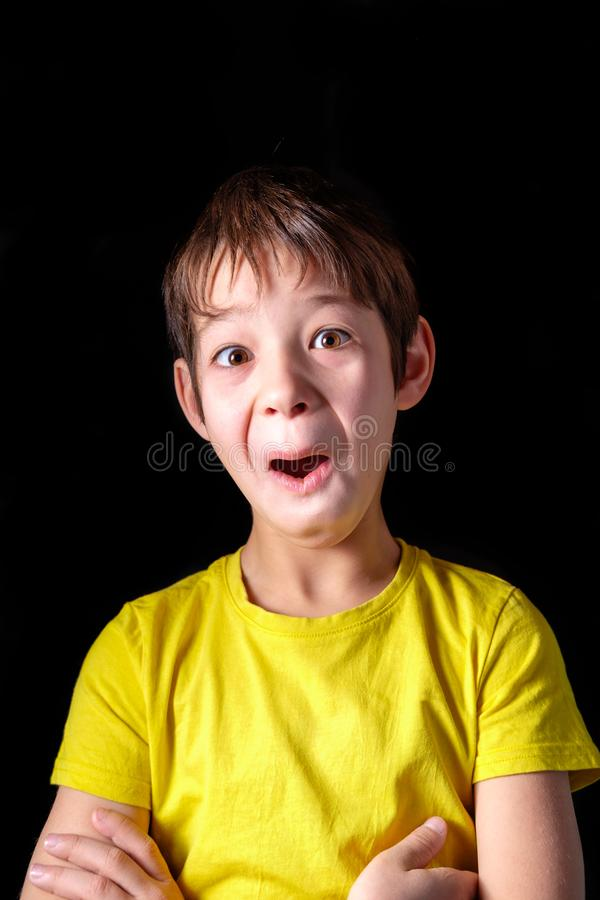 Boy in a yellow t-shirt makes funny faces royalty free stock photography