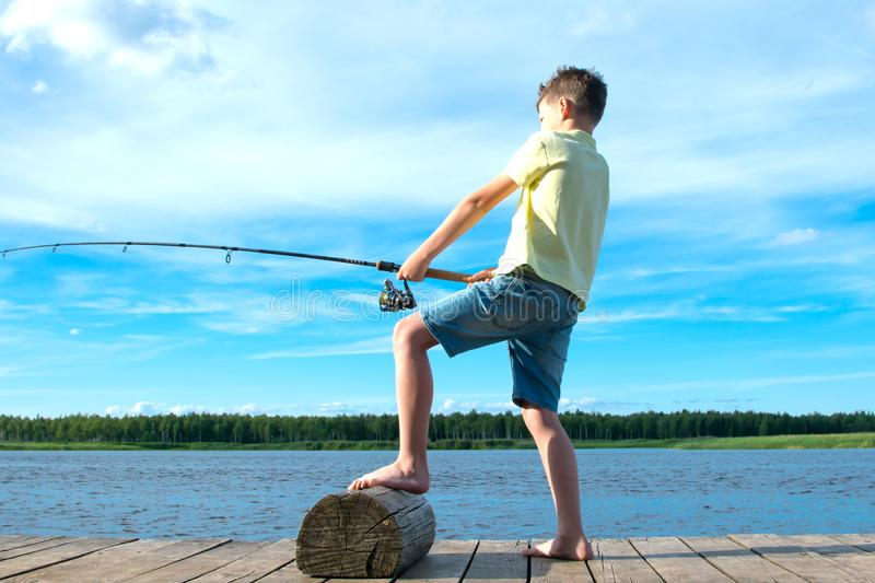 A boy in a yellow t-shirt, on the pier, against the blue lake and the sky,pulls the catch on a fishing rod stock photography