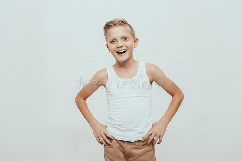 Young smiling boy in white tank top standing with hands on hips and looking at camera. Isolated on white stock photography
