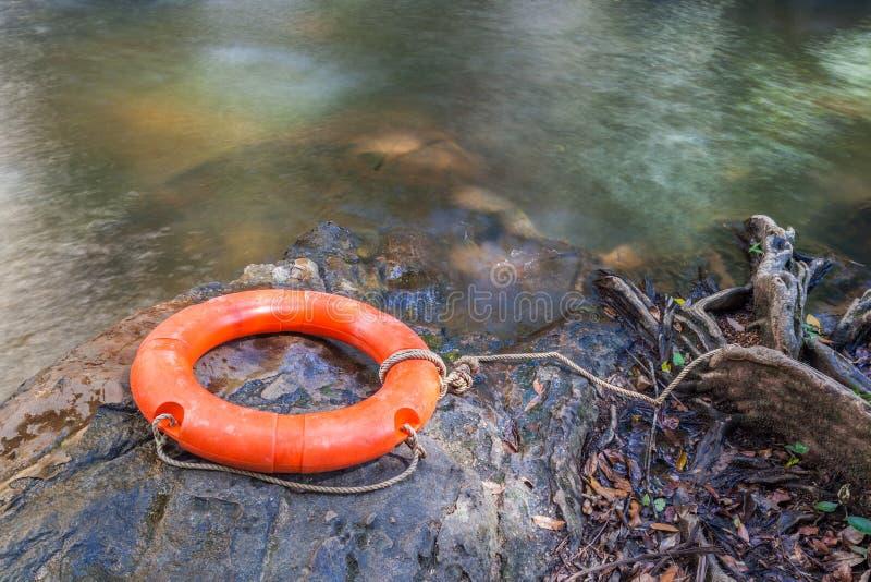 Boya de vida anaranjada sobre el agua clara de la corriente natural foto de archivo libre de regalías