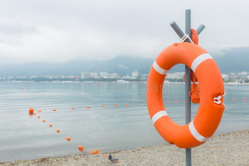 Boya de vida atada a un poste en la playa fotos de archivo