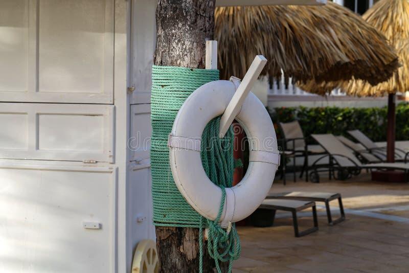 Boya de vida blanca que cuelga por la piscina fotos de archivo libres de regalías