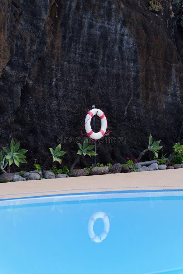 Boya de vida que cuelga en la pared rocosa oscura en la piscina fotografía de archivo libre de regalías