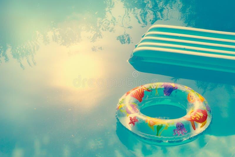 Boya inflada y colchón que flotan en el agua de una piscina Verano y concepto de los días de fiesta con el espacio ciopy imagen de archivo libre de regalías