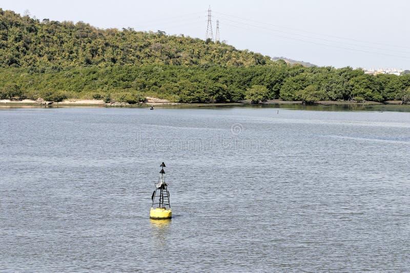 Boya moderna negra de la navegación con la raya amarilla que flota en un SE fotografía de archivo