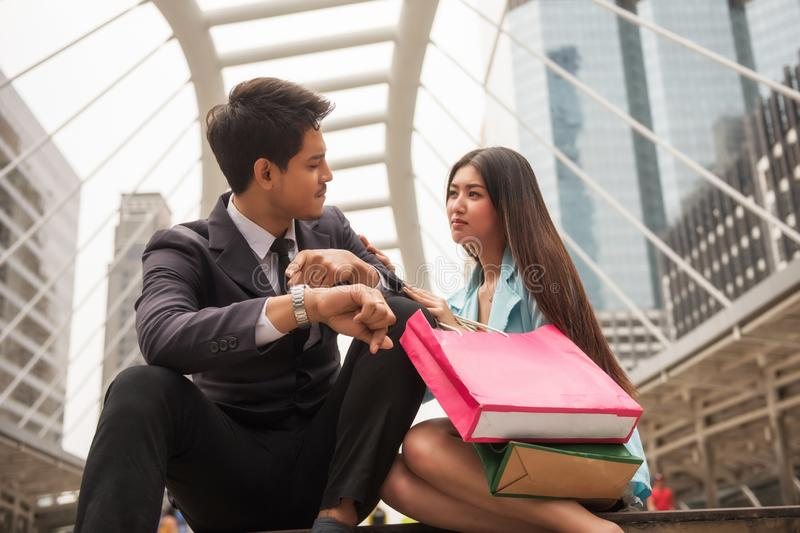 Boyfriend blame girlfriend late from shopping. Angry handsome businessman boyfriend point to watch to blaim his girlfriend to miss appointment time due to royalty free stock photo
