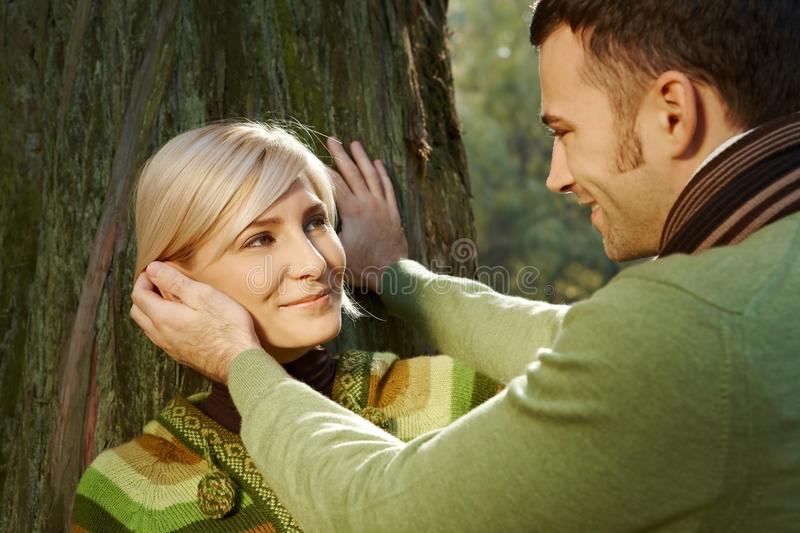 Boyfriend caressing happy romantic blond lady. Caucasian boyfriend caressing happy romantic blond lady leaning against tree at forest, outdoor. Smiling royalty free stock photo