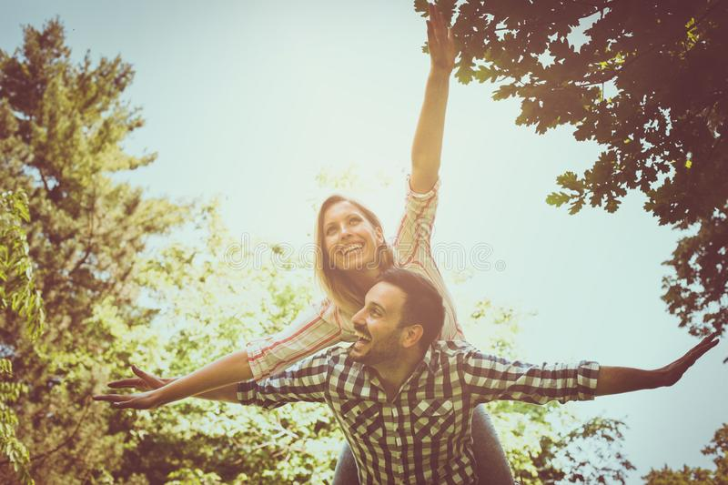 Boyfriend carries the girl on her piggyback with open arms. Cou royalty free stock photos