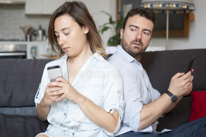Boyfriend caught by girlfriend while cheating with mobile phone. Relationship problem because of jealousy and infidelity royalty free stock photography