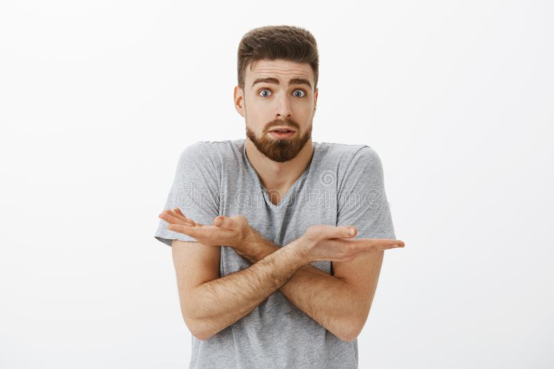 Boyfriend confused cannot understand what done wrong. Clueless and questioned charming brunet with beard and blue eyes. Shrugging with crossed arms opening stock images