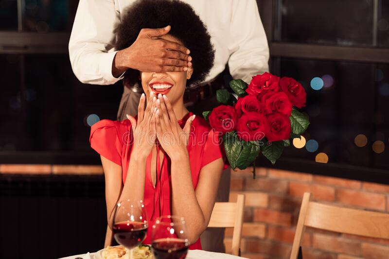 Boyfriend Covering Girlfriend`s Eyes Holding Roses Having Date In Restaurant. Valentine`s Romance. African American Boyfriend Covering Girlfriend`s Eyes Holding royalty free stock photography