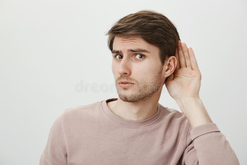 Boyfriend do not believe his couple and spying on her. Portrait of worried guy having trust issues, frowning and looking stock photography