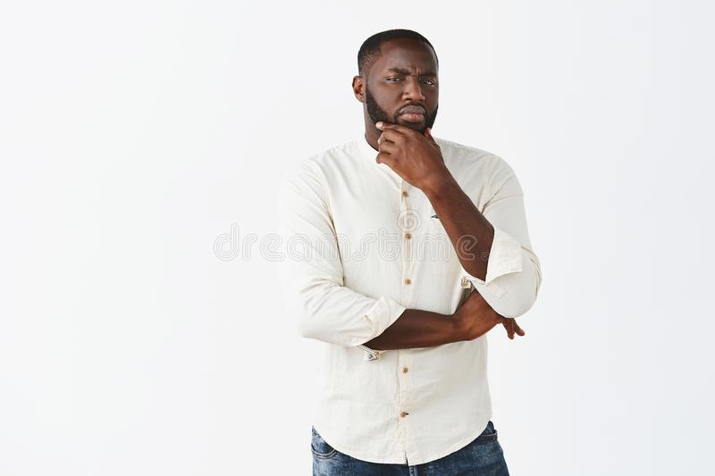 Boyfriend gets suspicious. Portrait of intense African American handsome man with beard staring doubtful and with royalty free stock images