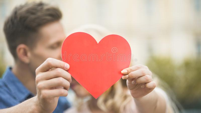 Boyfriend and girlfriend cuddling and hiding behind paper heart, romantic love stock photos