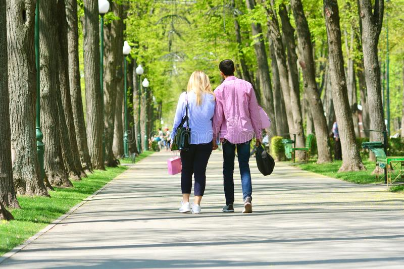 Boyfriend and girlfriend dating. Couple in love walking together along the park alley. stock image