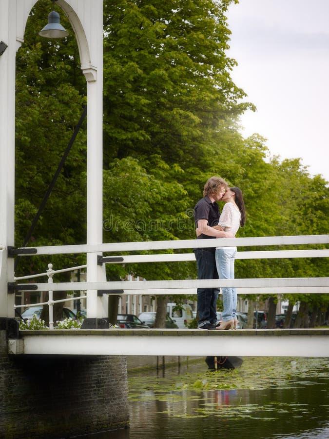 Boyfriend and girlfriend kissing on bridge royalty free stock photos