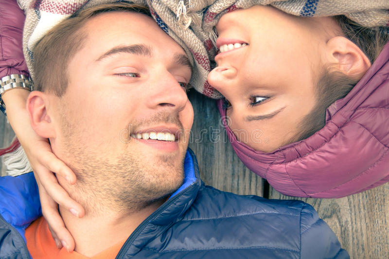 Boyfriend and girlfriend lying taking selfie outdoors with happy face expression looking each other in eyes. Couple of lovers stock photos