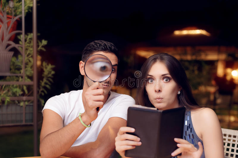 Boyfriend and Girlfriend Surprised by the Expensive Restaurant Bill royalty free stock photography
