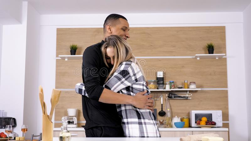 Boyfriend having a cute moment with his gilfriend while cooking stock photo