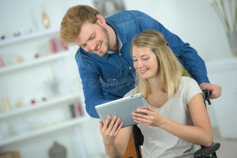Boyfriend helping girlfriend on wheelchair to use tablet royalty free stock images