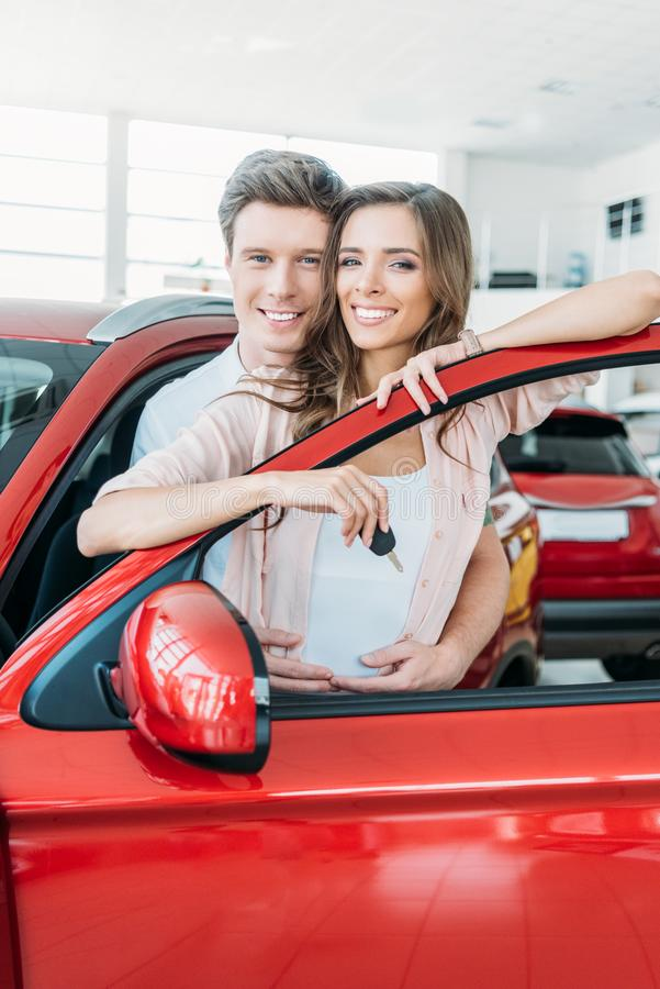 Boyfriend hugging his girlfriend from the back near red car in showroom while she holding. Car key royalty free stock image