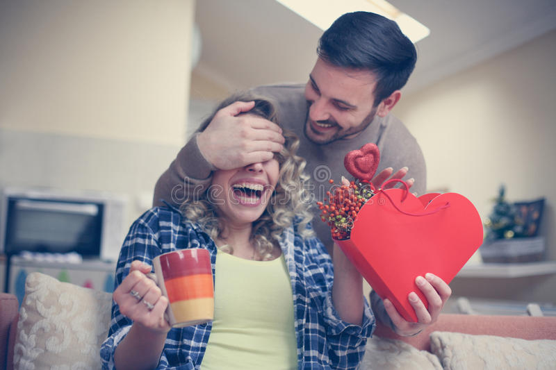 Boyfriend keeps eyes closed to his girlfriend. Young couple enjoying together at home. royalty free stock photography