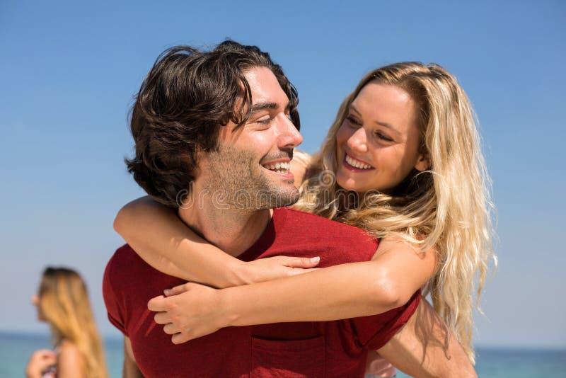 Boyfriend piggybacking girlfriend at beach against sky. Close-up of happy boyfriend piggybacking girlfriend at beach against sky stock photo