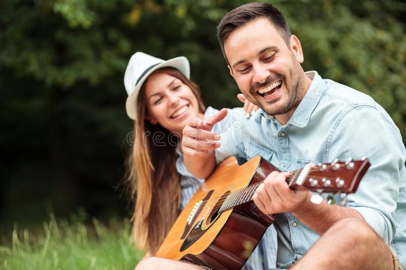 Happy young man playing guitar to his beautiful girlfriend royalty free stock image