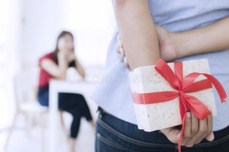 Boyfriend prepare gift to surprising girlfriends. Romantic husband and love concept stock photography