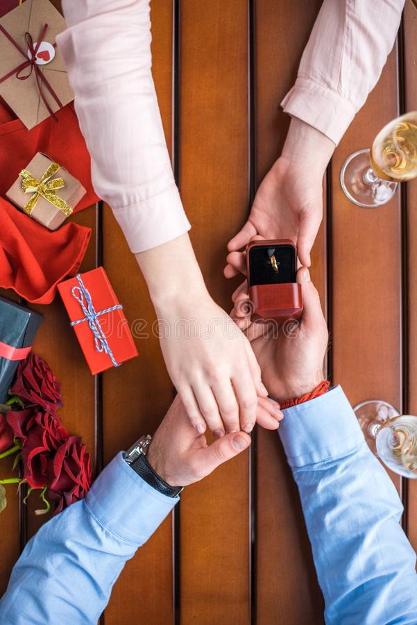 Boyfriend proposing girlfriend and holding hands. Cropped image of boyfriend proposing girlfriend and holding hands royalty free stock images