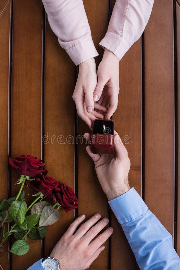 Boyfriend proposing girlfriend and holding wedding ring. Cropped image of boyfriend proposing girlfriend and holding wedding ring royalty free stock photos