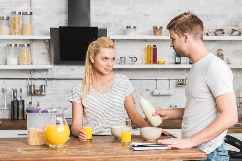 Boyfriend proposing milk to skeptical girlfriend. In kitchen royalty free stock images