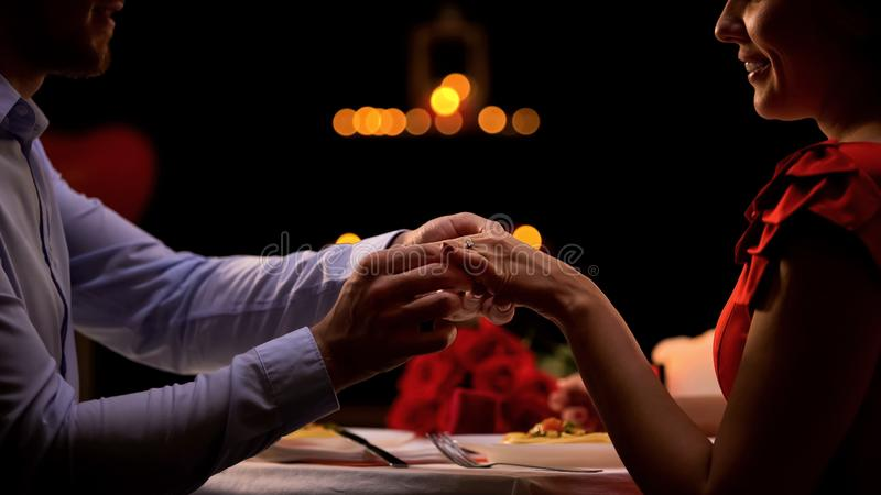 Boyfriend putting precious ring on female finger, couple enjoying romantic date royalty free stock photos