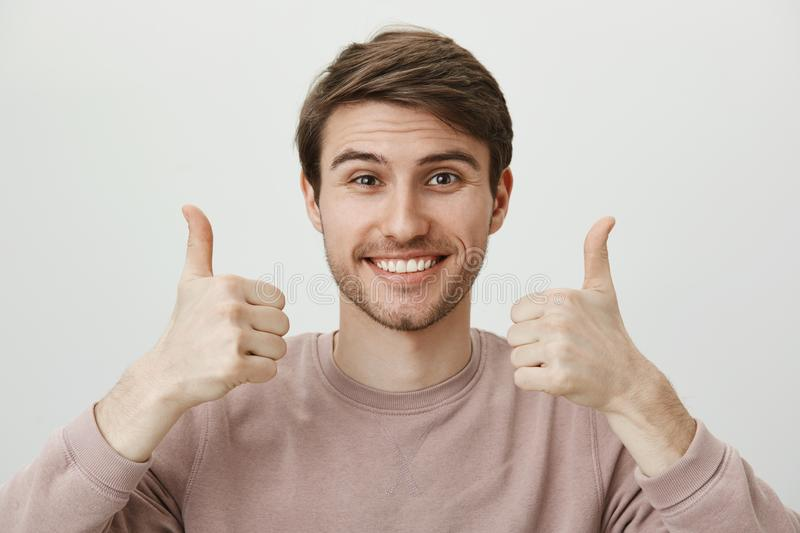 Boyfriend supports girlfriend on match. Happy attractive european guy with bristle in trendy clothes smiling cheerfully. And showing thumbs up gesture, giving stock photography