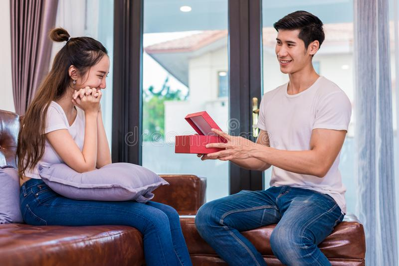 Boyfriend surprising girlfriend with present. Woman surprised when looking at gift box on special day. Lovers and Couples concept. Honeymoon and Dating theme royalty free stock photos