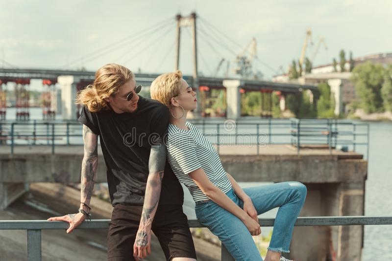 Boyfriend with tattoos and stylish girlfriend. Touching with backs and sitting on railing of bridge royalty free stock images