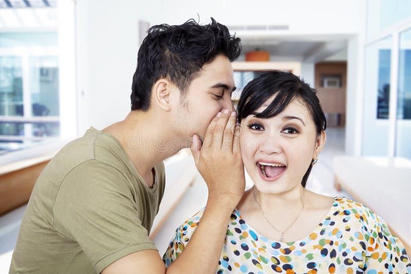 Boyfriend tell secret to girlfriend at home stock photo