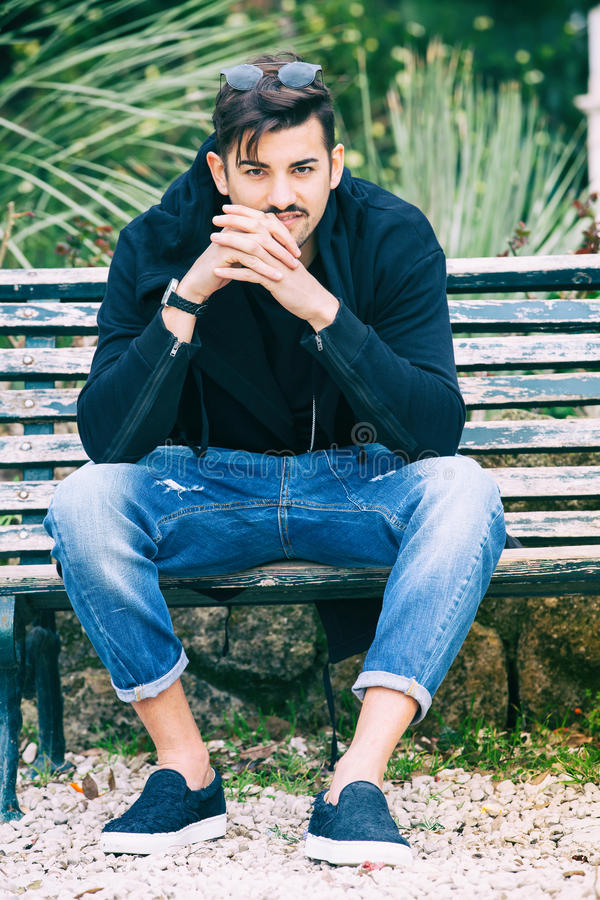 Boyfriend waiting. Handsome young man model sitting on the bench stock photography