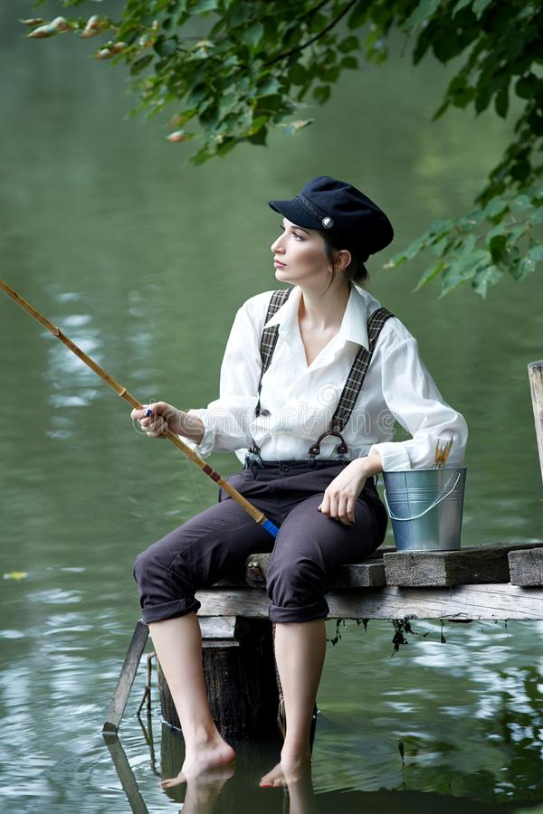 Boyish looking girl fishing outdoors. Old school stock photos