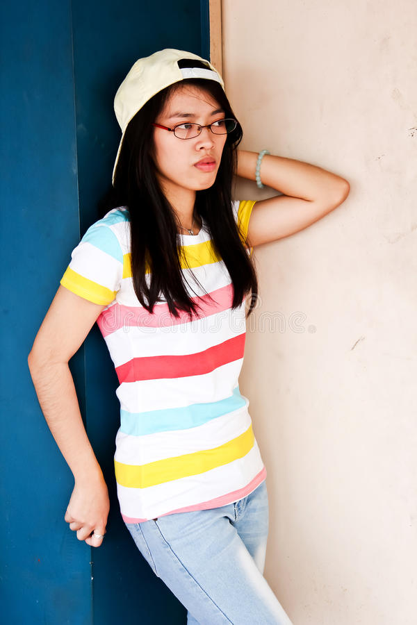 Boyish Pretty young Asian girl with glasses. A photograph of a boyish pretty young girl with glasses wearing a striped shirt and jeans leaning on a wall royalty free stock images