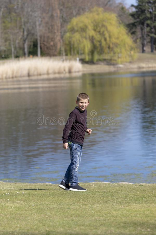 The boyl is walking along the shore of the lake in the spring royalty free stock images