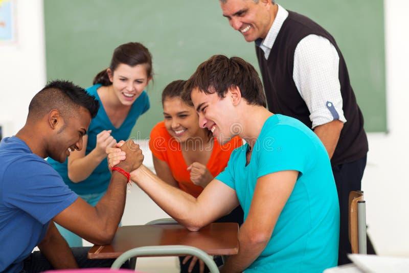 Boys arm wrestling. High school teenage boys arm wrestling in classroom stock images