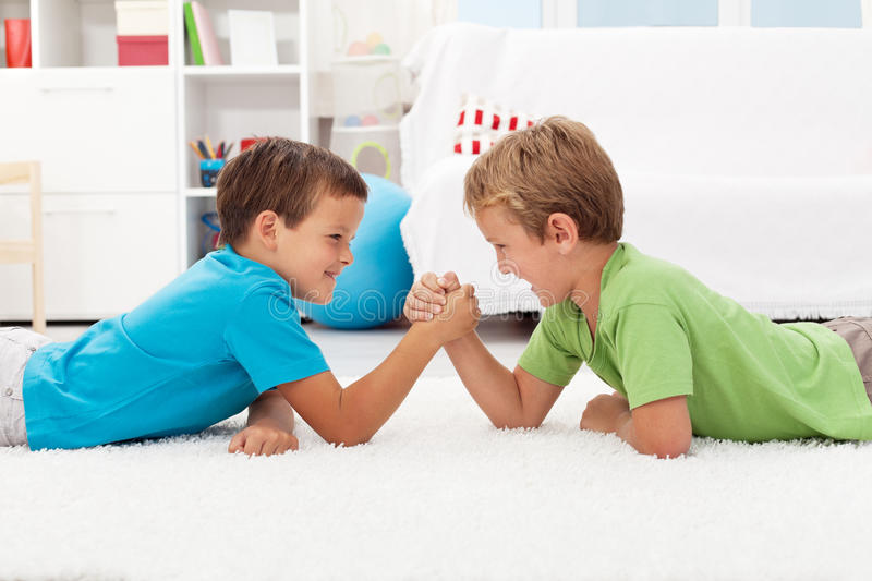 Boys arm wrestling in the kids room. Childhood rivalry stock image