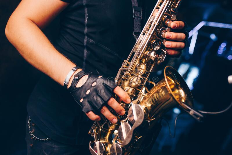 Boys Band saxophone section at event , jazz player male playing on Saxophone, music instrument played by man saxophonist. Musician at  folk classical . Alto stock photo